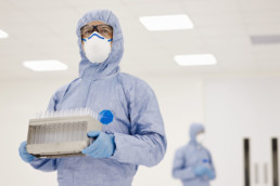 ACE - Scientist carrying tray of test tubes in laboratory